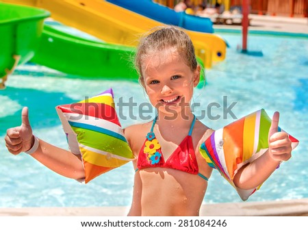 Child with colored armbands playing in swimming pool. Summer outdoor. - stock photo