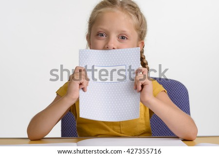 Child with copybook. Lovely little princess shows her stationery and looks right in the camera with her big blue eyes. White background in the studio. - stock photo