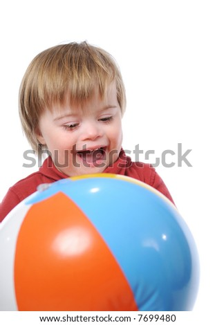 Child with down syndrome playing with a ball - stock photo