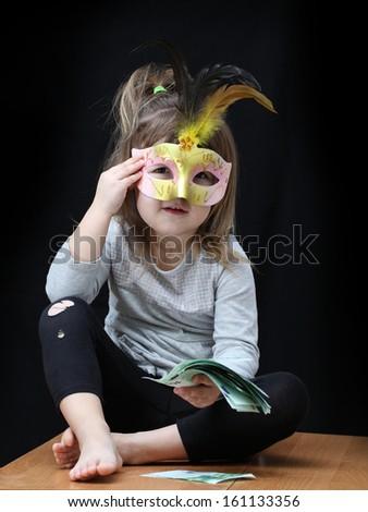 Child with euro money on black background - stock photo