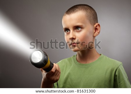 Child with flashlight looking to find answers, studio concept shot - stock photo