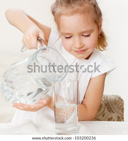Child with glass pitcher water. Little girl drinking water at home - stock photo