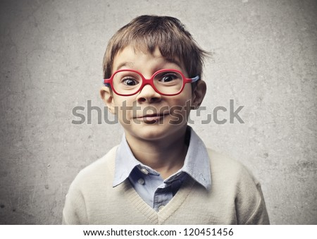 Child with glasses is surprised by something or someone - stock photo