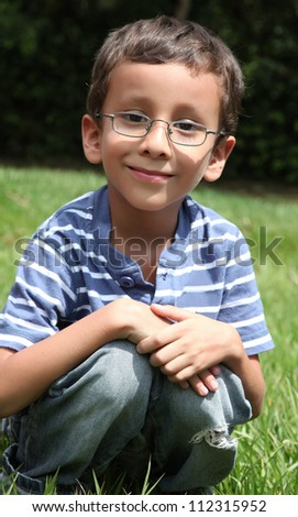 child with glasses looking at the camera with a natural background - stock photo
