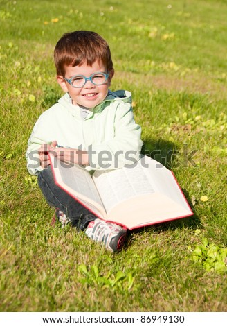 Child with glasses reading a book sitting on grass - stock photo