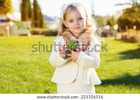 Child with green apples sitting on grass - stock photo