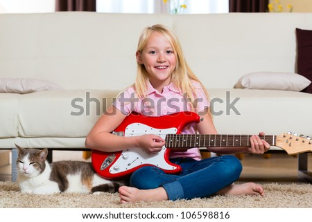 Child with guitar making music at home in the living room - stock photo