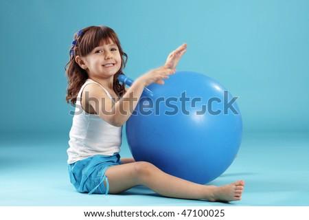 Child with gymnastic ball on bleu studio background - stock photo