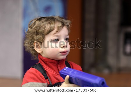 Child with handgun at an amusement park - stock photo