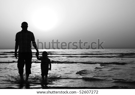 child with his father at sea. Sunset - stock photo