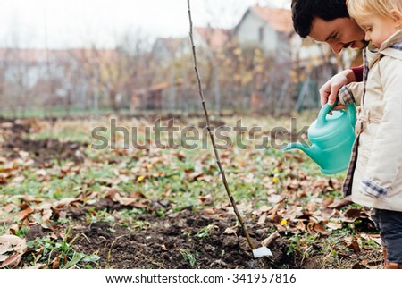 Child with his father  watering planted seedling - stock photo