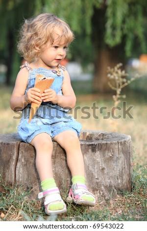 Child with ice-cream sitting on stump - stock photo
