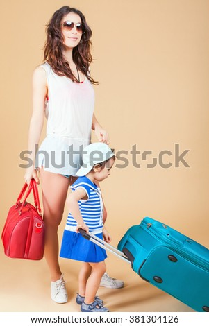 Child with mother ready travel to Europe, Italy. Family carries luggage at white background. Vacation rentals, packages. Airport terminal. Suitcase. Tourism. Tourist bag. - stock photo