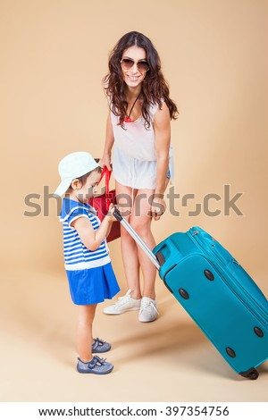 Child with mother ready travel to Europe, Milan. Family carries luggage at white background. Vacation rentals, packages. Airport terminal. Suitcase. Tourism. Tourist bag.