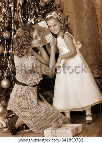 Child with mother receiving gifts under Christmas tree and laughing . Black and white retro. - stock photo