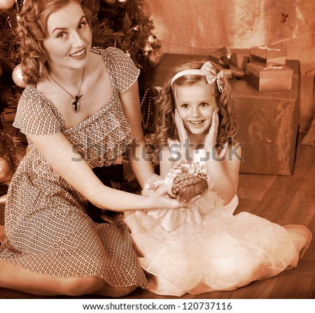 Child with mother receiving gifts under Christmas tree. Black and white retro. - stock photo