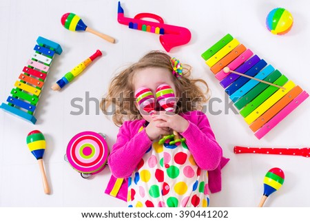 Child with music instruments. Musical education for kids. Colorful wooden art toys for kids. Little girl playing music. Kid with xylophone, guitar, flute. - stock photo