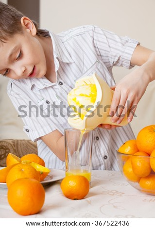Child with oranges. Boy squeezed orange juice.