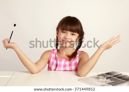 Child with paint brush covered in paint and isolated on white. - stock photo