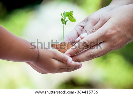 Child with parents hand holding young tree in egg shell together for prepare plant on ground,save world concept
