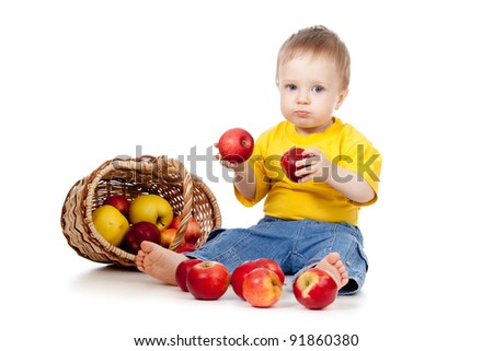 child with red apples; near basket - stock photo