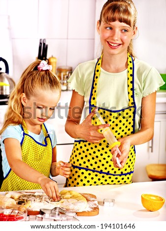 Child with rolling-pin dough at kitchen. - stock photo