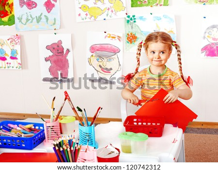Child with scissors cut  paper  in playroom. Preschool.