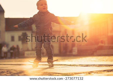 Child with skateboard on the street at sunset light. - stock photo