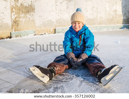 Child with skates sits and have fun in  the outdoor rink.  Wide ange close up  shoot.  - stock photo