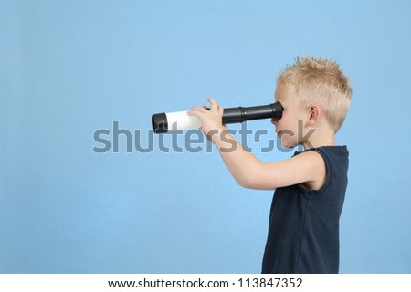 child with spyglass on  blue - stock photo