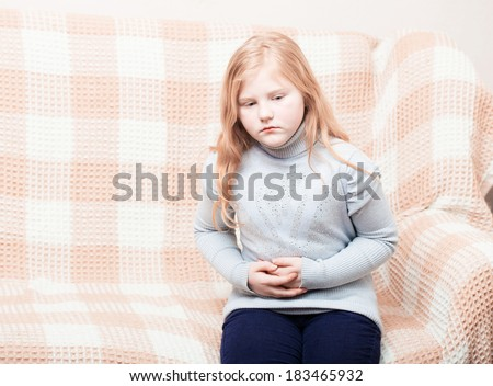 child with stomach ache in sofa - stock photo