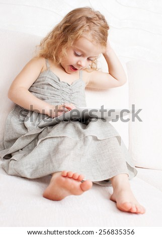 Child with tablet computer. Girl with pc at home - stock photo