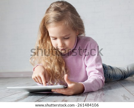 Child with tablet lying on floor. Girl playing laptop computer - stock photo