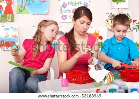 Child with teacher in play room. Preschooler. - stock photo
