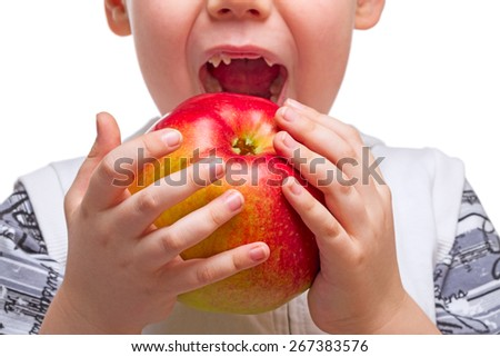 Child with teeth dropped out to bite an apple. The child is not in focus and recognizable - stock photo