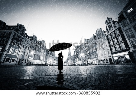 Child with umbrella standing alone on cobblestone old town in rain. Concept of being lost, lonely in a big world or exploring - stock photo