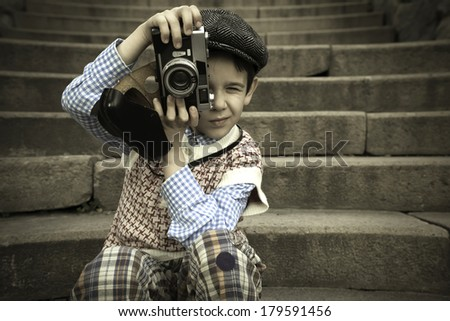 Child with vintage camera. Exterior stairs