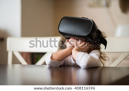Child with virtual reality headset sitting behind table indoors at home - stock photo