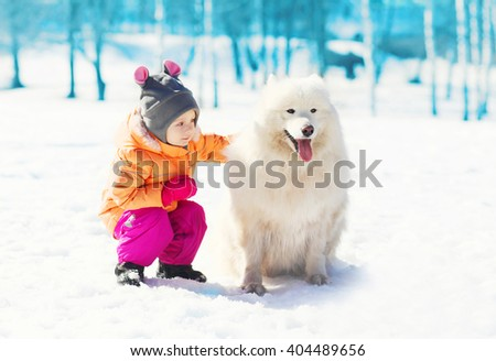 Child with white Samoyed dog on snow in winter day