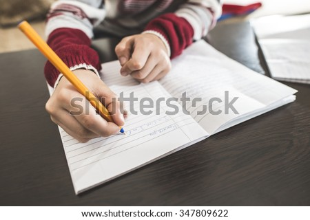 Child write in a notebook. Close up hand and pen