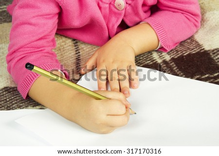 Child writes a pencil on a blank white sheet
