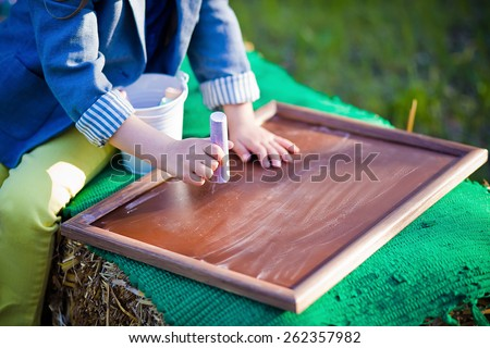 child writes on the chalkboard - stock photo