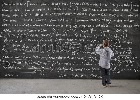 Child writing on a blackboard - stock photo