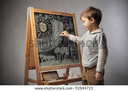 Child writing on a blackboard - stock photo