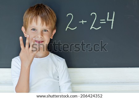 child writing sum on blackboard - stock photo