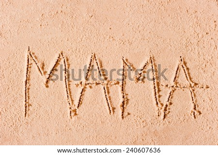 child wrote the word mom in the sand on the beach - stock photo