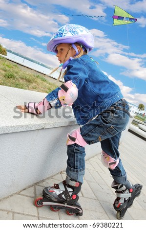 Child 5 years old studying rollerblading in the park against the blue sky with a kite in it. - stock photo