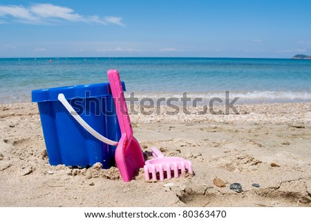 Childen's toy on the sand beach by the sea - stock photo