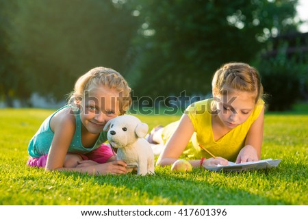 Childhood and nature. Playing with toys and drawing pictures outdoors is very important for children's upbringing. Two little sisters on green grass in park. - stock photo