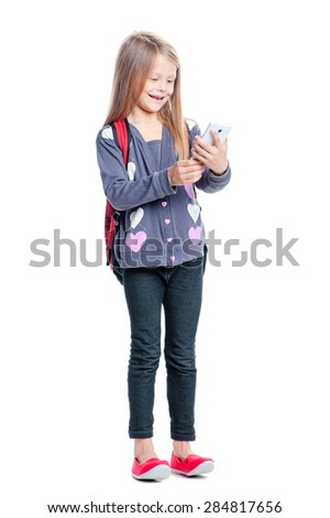 Childhood and technology. Full length of pretty little girl standing with backpack using smartphone. Isolated on white. - stock photo